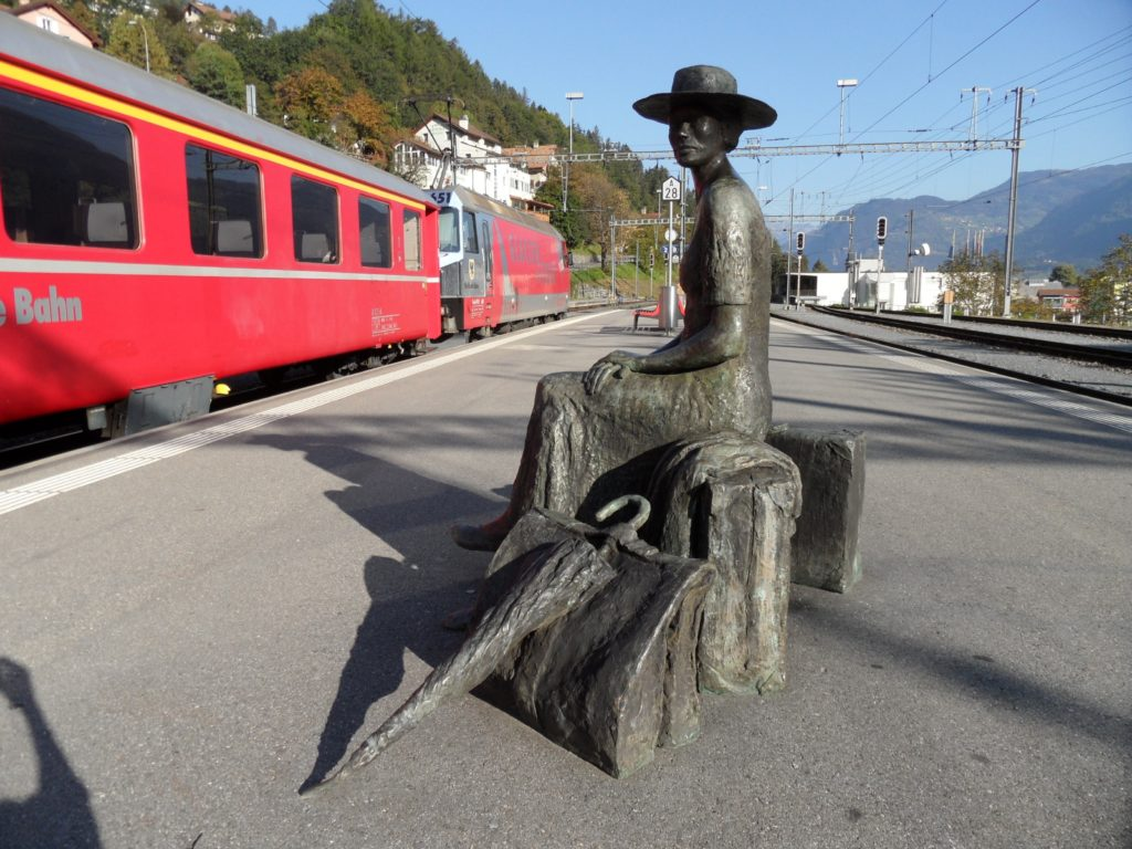 statue of a woman on a bench with umbrella waiting for the train, switzerland, glacier express