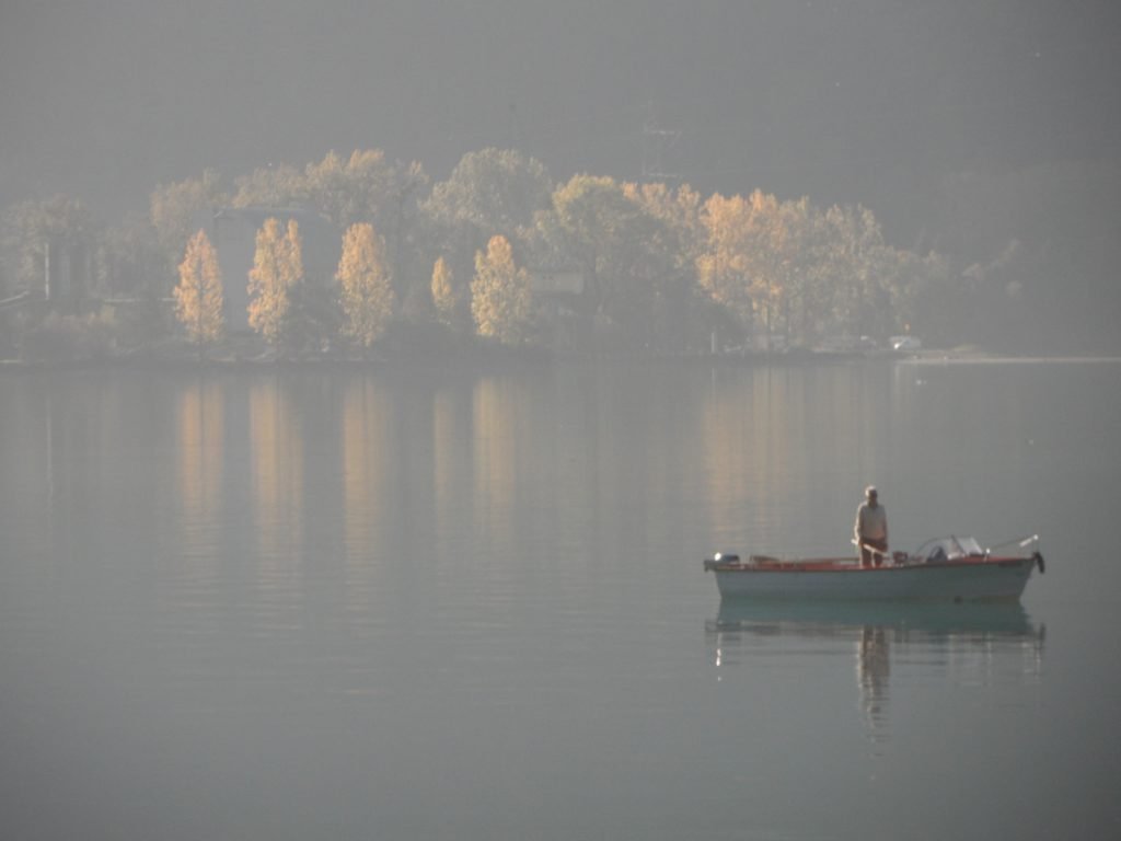 man in boat fishing on a lake in switzerland reflections